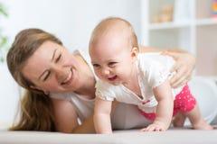 Bébé de rampement heureux avec la mère Photographie stock