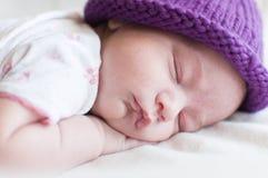 Bébé de sommeil dans le chapeau pourpre Photographie stock