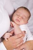 Bébé de sommeil de fixation de mère dans des ses bras Photos stock