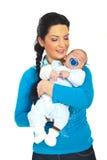 Bébé de sommeil de fixation heureuse de mère Photo stock