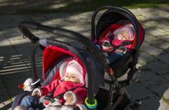 Bébé de sommeil de jumeaux dans la double poussette images stock