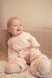Bébé de sourire drôle s'asseyant sur le sofa sur le fond beige Photographie stock libre de droits