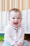 Bébé de sourire heureux contre le lit blanc Photo libre de droits