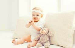 Bébé de sourire heureux jouant à la maison dans la chambre blanche Photos stock
