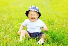 Bébé de sourire heureux s'asseyant sur l'herbe en été ensoleillé Image stock