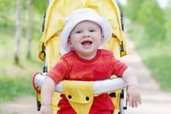 Bébé de sourire heureux sur la voiture d'enfant jaune Photo stock