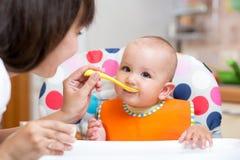 Bébé de sourire mangeant de la nourriture avec la maman sur la cuisine images stock