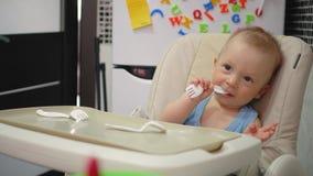 Bébé de sourire mangeant de la nourriture sur la cuisine Bébé s'asseyant dans la chaise d'arbitre avec la cuillère et le plat sur banque de vidéos