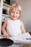 Bébé de sourire maniant maladroitement la magazine Photo libre de droits