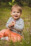 Bébé de sourire s'asseyant dans la forêt Photographie stock