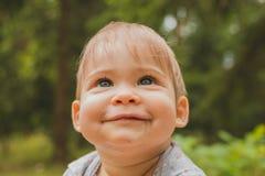 Bébé de sourire s'asseyant dans la forêt Photographie stock libre de droits