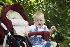 Bébé de sourire s'asseyant dans la poussette Photographie stock