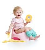 Bébé de sourire s'asseyant sur le pot de chambre Images libres de droits