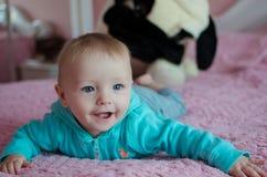 Bébé de sourire se situant dans le lit des pearent photo libre de droits