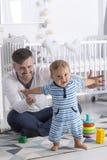 Bébé de soutien de papa faisant des premières étapes image libre de droits