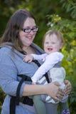 Bébé de transport de maman avec le transporteur, appréciant le jour en parc photographie stock libre de droits