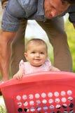 Bébé de transport de père dans le panier de blanchisserie image stock