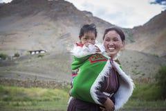 Bébé de transport de femme indienne sur elle de retour en vallée de spiti Photographie stock libre de droits