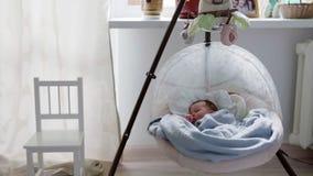 Bébé dormant dans le berceau de oscillation banque de vidéos