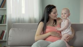 Bébé doux adorable étreignant sa maman, amour et soin enceintes dans la famille banque de vidéos