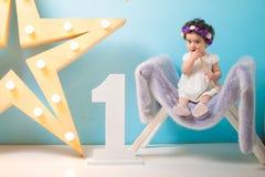 Bébé doux de sourire heureux s'asseyant sur le fauteuil avec briller l'étoile légère, fille d'anniversaire, d'un an photo stock