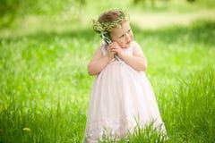 Bébé doux dehors avec un bouquet des lis Photo libre de droits