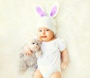 Bébé doux heureux dans le chapeau tricoté avec le jouet d'oreilles de lapin et d'ours de nounours Photo libre de droits