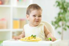 Bébé drôle mangeant de la nourriture saine dans la garde photographie stock