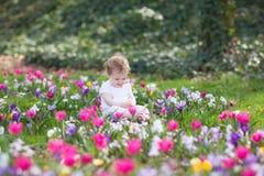 Bébé drôle de Bautiful jouant dans le domaine des fleurs Photo stock