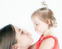 Bébé drôle en gros plan et sa mère sur le fond blanc Image stock