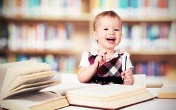Bébé drôle en verres lisant un livre dans une bibliothèque Photo stock