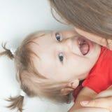 Bébé drôle se trouvant près de la mère heureuse sur le lit blanc Image stock