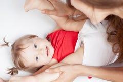 Bébé drôle se trouvant près de la mère heureuse sur le lit blanc Images libres de droits