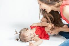 Bébé drôle se trouvant près de la mère heureuse sur le lit blanc Photographie stock