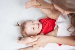 Bébé drôle se trouvant près de la mère heureuse sur le lit blanc Image libre de droits