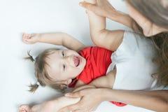 Bébé drôle se trouvant près de la mère heureuse sur le lit blanc Photographie stock libre de droits