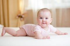 Bébé drôle se trouvant sur le lit image stock