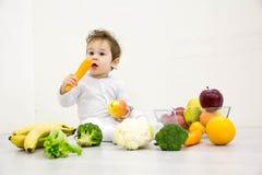 Bébé entouré avec des fruits et légumes, nutrition de l'enfant saine image libre de droits