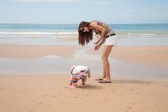 Bébé et mère recherchant des coquilles de mer Image stock
