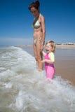 Bébé et mère riant avec des vagues Photos stock