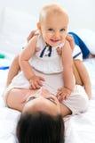 Bébé et sa mère jouant à la maison Photos stock
