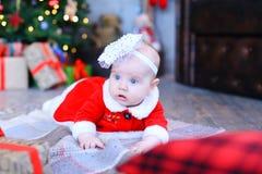 Bébé féminin européen se trouvant sur le plancher près de l'arbre et des présents de Noël photographie stock