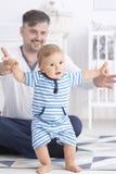 Bébé faisant des premières étapes avec le père photo libre de droits