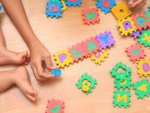 Bébé faisant le puzzle Le puzzle d'enfant développe des enfants Participation d'enfant photographie stock