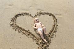 Bébé fixant dans la copie de forme de coeur sur le sable. Image libre de droits