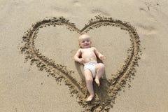 Bébé fixant dans la copie de forme de coeur sur le sable. Photo stock