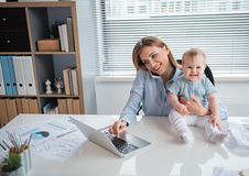 Bébé gai et maman travaillant au bureau photos libres de droits
