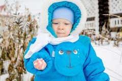 Bébé garçon étonné avec la première neige tenant la neige à sa main Photographie stock