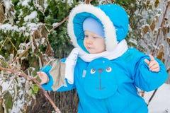 Bébé garçon étonné avec la première neige tenant la neige à sa main Photo libre de droits
