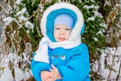 Bébé garçon étonné avec la première neige tenant la neige à sa main Photos libres de droits